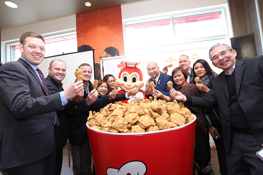 Jollibee executives and special guests gather around a giant bucket of fried chicken for the Jolly Crispy Chicken toast. Seen here are JFC Group President for North America and Foreign Franchise Brands Jose Miñana, VP and General Manager of Jollibee North America Maribeth dela Cruz, Honorary Consul Ronald Opina, Member of the Legislative Assembly for St. Norbert Jon Reyes, President of Sysco Winnipeg Blair Schmidt, Trevor Skinner, and other special guests. (Photo courtesy of Jollibee)
