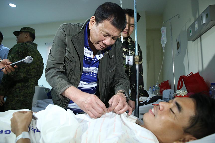 President Rodrigo Roa Duterte confers the Wounded Personnel Medal to one of the soldiers who were wounded in action during his visit to the Polymedic Medical Plaza in Kauswagan, Cagayan de Oro City on November 30, 2016. KARL NORMAN ALONZO/Presidential Photo