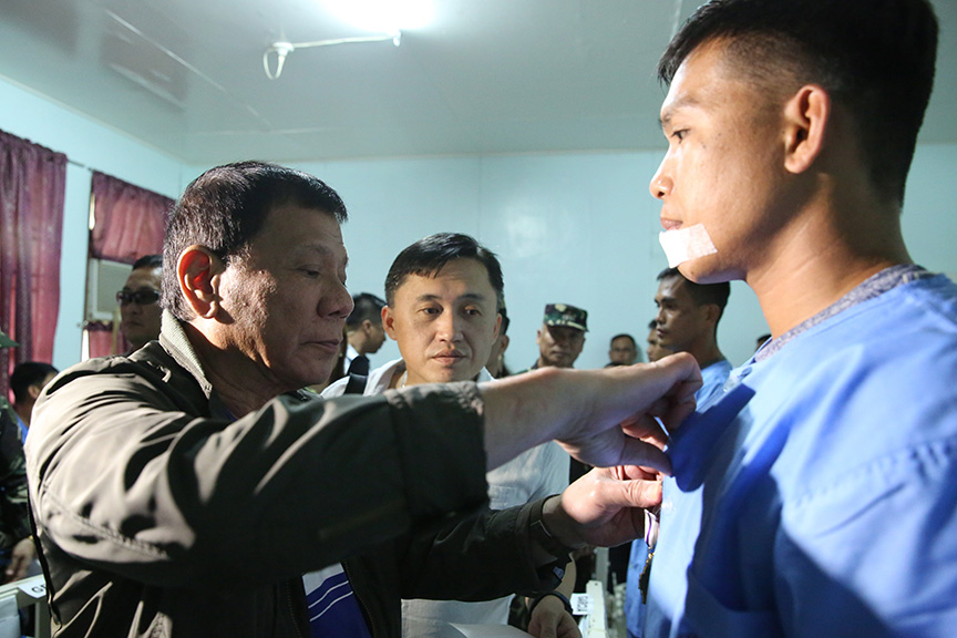 President Rodrigo Roa Duterte salutes to one of the five Presidential Security Group (PSG) members and one soldier who were wounded-in-action (WIA) during his visit to Camp Evangelista Station Hospital of the Philippine Army's 4th Infantry Division in Patag, Cagayan de Oro City on November 30, 2016. KARL NORMAN ALONZO/Presidential Photo