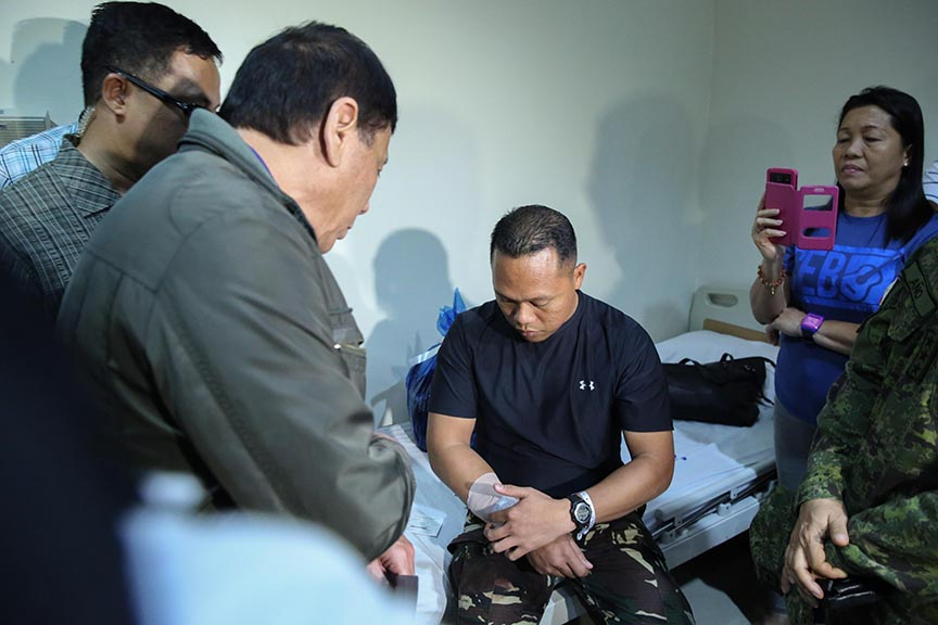 President Rodrigo Roa Duterte checks the condition of one of the five members comprising the Presidential advance party who were wounded in action during his visit to the Polymedic Medical Plaza in Kauswagan, Cagayan de Oro City on November 30, 2016. KARL NORMAN ALONZO/Presidential Photo