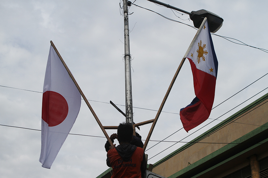DPWH personnel on Tuesday install flags on of Philippines and Japan along JP Laurel Avenue, Davao City ahead of the visit of Japan Prime Minister Shinzo Abe on Friday in the city. CONTRIBUTED PHOTO