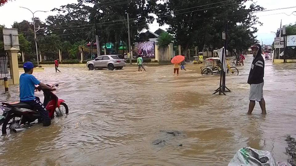 Local folks wade through the floodwaters in the town proper of Kapalong, Davao del Norte on Tuesday morning. Continuous rains in the region have inundate various parts of the province. Photo courtesy of Phoebie Graza