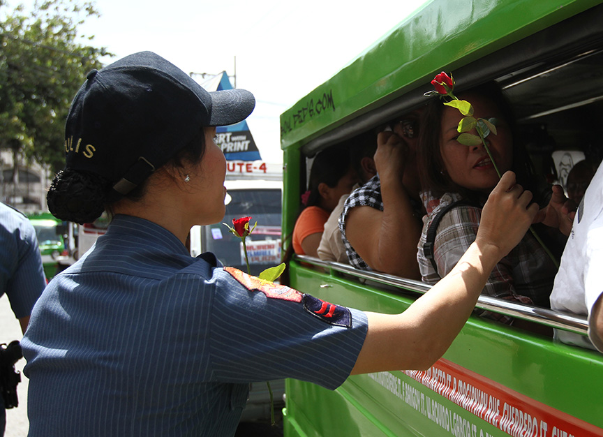 Members of the Davao City Police Office distribute flowers to commuters along San Pedro Street on Valentines Day, February 14. Newsline Photo