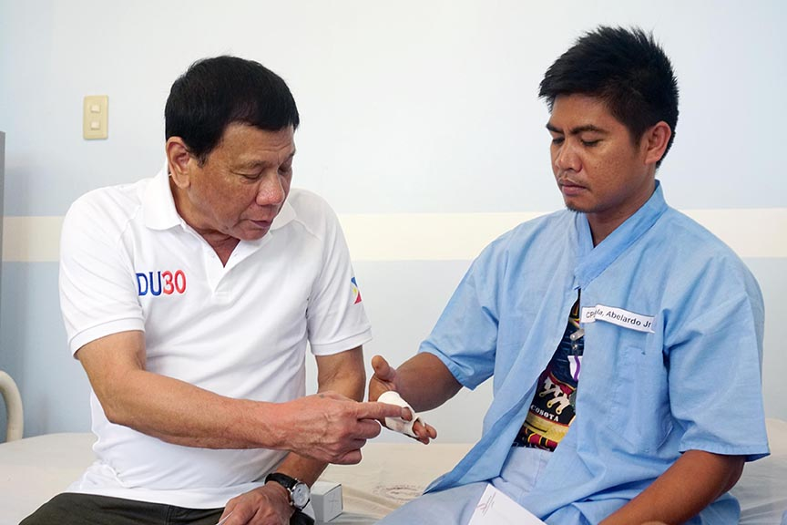 President Rodrigo Duterte examines the injuries of Corporal Abelardo Suela Jr., one of the soldiers wounded in an encounter with the New People's Army at Brgy. Lamanan in Calinan District, Davao City on February 16, 2017. The President personally visited the wounded soldiers at Camp Panacan Station Hospital in Davao City on February 17, 2017 to award them with Wounded Personnel Medals as well as cash assistances. PCOO Davao