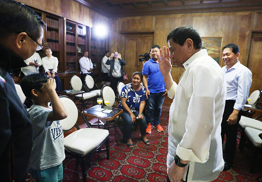 President Rodrigo Roa Duterte, during a meeting at the Malacañan Palace on February 28, 2017, salutes to Rexon Romoc, an eight year-old boy who was released from his Abu Sayyaf abductors on February 27, 2017 after seven months in captivity. KING RODRIGUEZ/Presidential Photo