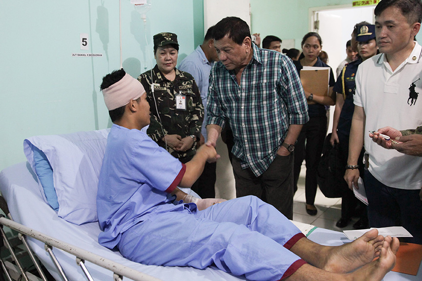 President Rodrigo Roa Duterte shakes the hands of 2Lt. Daniel De Guzman, one of the soldiers wounded-in-action in an encounter with the New Peoples Army recently. The President awarded the Wounded Personnel medal to the soldiers during his visit at Camp Evangelista Station Hospital in Cagayan de Oro City on March 3, 2017.ALBERT ALCAIN/Presidential Photo
