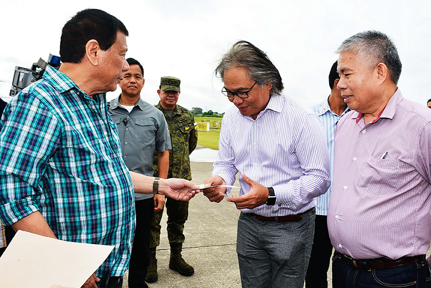President Rodrigo Roa Duterte hands a check worth P192.5-million to Southern Philippines Medical Center (SPMC) Chief Dr. Leopoldo Vega at the Tactical Operations Group (TOG)-11 in Sasa, Davao City on March 3, 2017. The check is the first tranche for the P385-million needed to improve the facilities of SPMC. RENE LUMAWAG/Presidential Photo