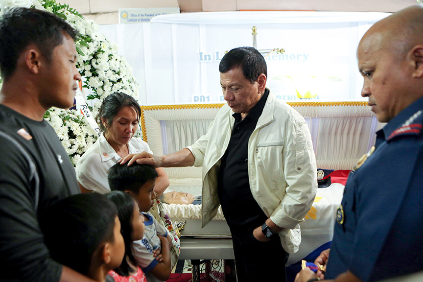 President Rodrigo Roa Duterte comforts one of the children of the late PO1 Rholly Benelayo during his wake visit at the Bansalan Municipal Lobby in Davao del Sur on March 9, 2017. Benelayo is one of the four police officers who were killed in an ambush by suspected members of the New People's Army in the municipality of Bansalan, Davao del Sur on March 8, 2017. Also in the photo is Philippine National Police Director General Ronald dela Rosa. ROBINSON NIÑAL/Presidential Photo