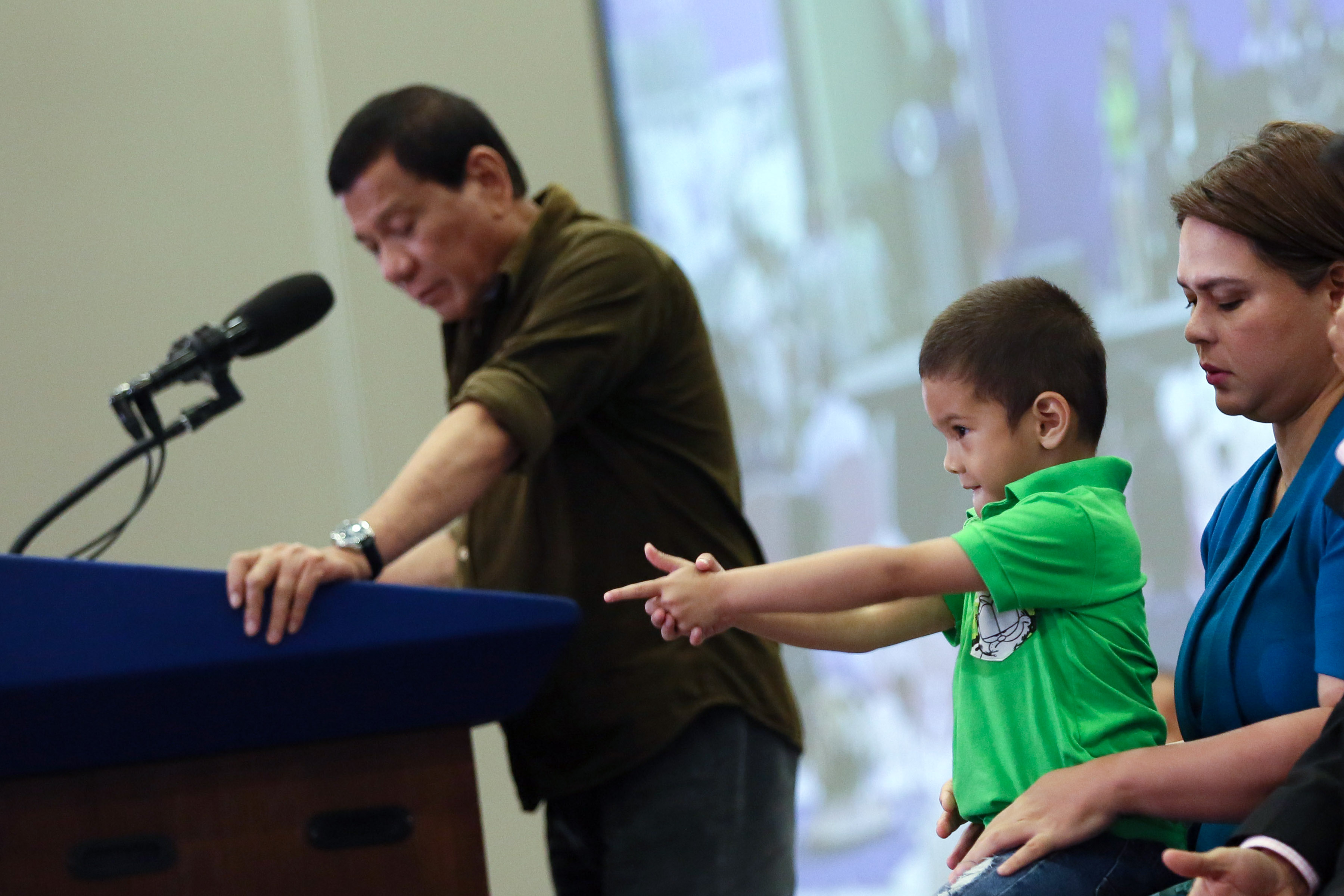 POSING LIKE A PRO: Stingray, the grandson of President Rodrigo Duterte (in green polo) pose like enjoying his fingers holding a gun while his grandfather talks about imposing stiffer government regulations to gun buyers.-PHOTO: PPD
