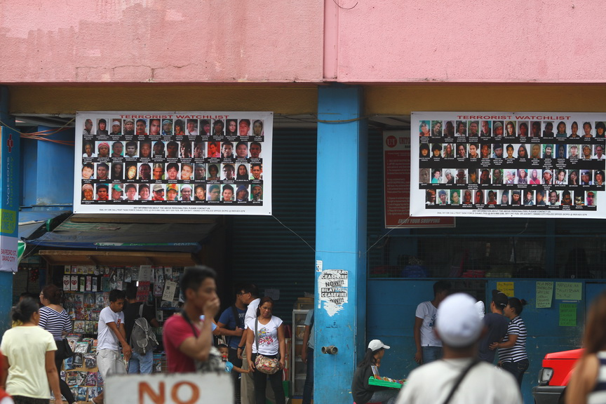Streamers printed with the pictures of suspected local terrorists posted outside a business establishment along San Pedro Street in Davao City.  Newsline Photo