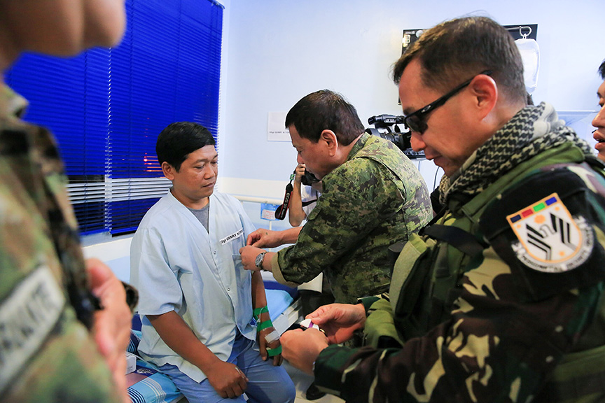 President Rodrigo Roa Duterte awards a wounded personnel medal to Staff Sergeant Gerry Torsal during the President's visit to Camp Panacan Station Hospital in Davao City on July 20, 2017. Torsal was one of the Presidential Security Group (PSG) personnel wounded in an encounter against the New People's Army in Arakan, North Cotabato on July 19. ALBERT ALCAIN/PRESIDENTIAL PHOTO